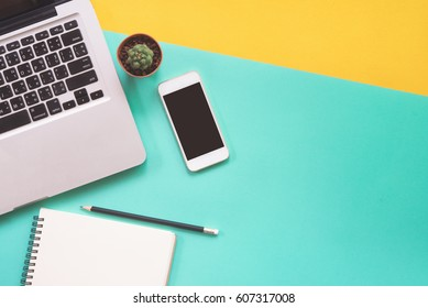 Flat lay design of work desk with labtop notebook, smartphone and cactus on green and yellow background.