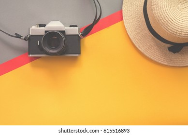 Flat lay design of work desk with old camera and straw hat on Retro background.