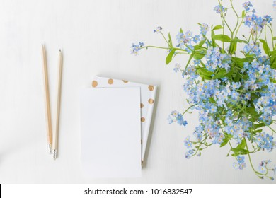Flat lay desk with with blue flowers on light background