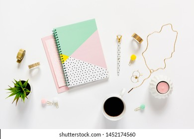 Flat lay desk table. Workspace with modern notebook, stationery, succulent, jewelry and a cup of coffee on white table. Top view. Feminine concept