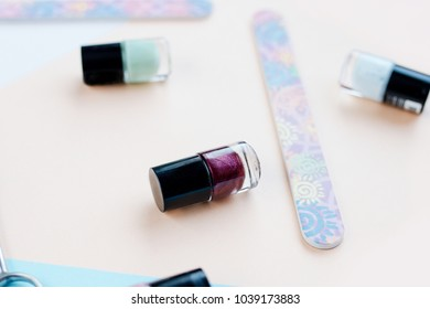 Flat lay with different nail poliish colors on pastel background