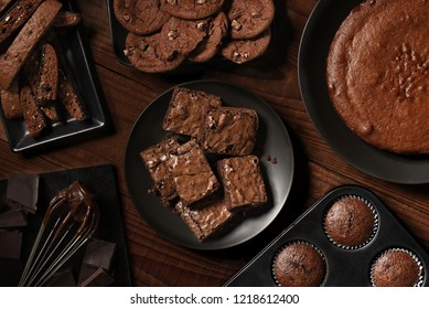 Flat Lay display of fresh baked choclate desserts on black plates and a rustic wood table. Items include, Biscotti, Cake, Muffins, Brownies, and Cookies.