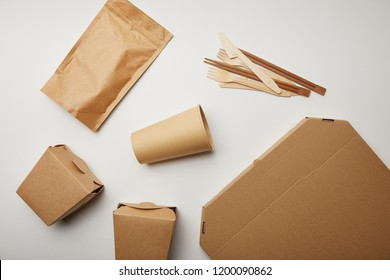 flat lay of disposable knives with forks, paper coffee cup and food boxes on white surface