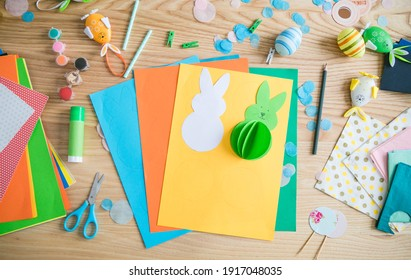 Flat lay with DIY paper Easter bunnies and colorful paper, easy crafts for kids.
