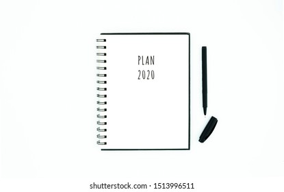 Flat lay to do 2020 list plan still life concept mockup opened spiral notebook and black pen on white background