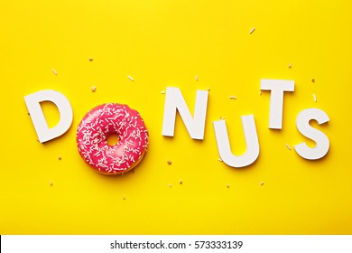 Flat lay donuts letters on a yellow background. Top view