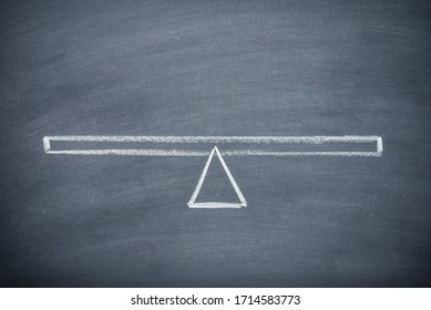 Flat lay of drawing empty seesaw or balance scale in equilibrium on chalkboard or blackboard background with copy space. Concept of decision, comparison and measuring.