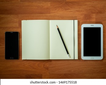 Flat lay of educating tool set include smarthphone , notebook with pencil and tablet on wooden desk
