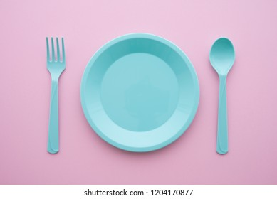 Flat lay of empty blue pastel plastic dish, spoon and fork on pink background. Minimal simple color style. Food and drink restaurant accessories utensil on table concept.
