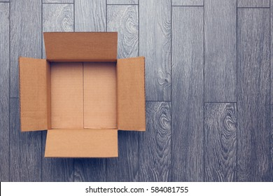 Flat lay of empty open cardboard box on wooden surface with empty space