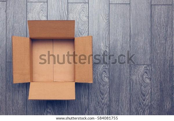 Flat lag leerer offener Karton auf Holzfläche mit Leerraum