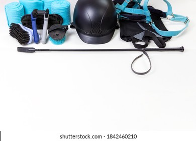 Flat lay of equestrian gear: helmet, brushes, whip, bandages, pads, dressage, bridle. Accessories and equipment for horse care and riding on the white background with copy space for yout text
