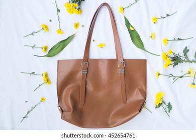 Flat lay Fashion bag with flowers on White Fabric Texture background.