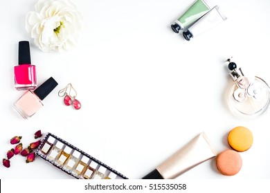 Flat lay for fashion blogger. Woman's glamour makeup beauty products on a white background. Foundation, nail polishes, earings, set of perfumes, flowers, macarons. Elegant style. Copy space for text