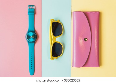 Flat lay fashion set: blue watch, pink purse and yellow sunglasses on yellow, pink and mint background in pastel colors