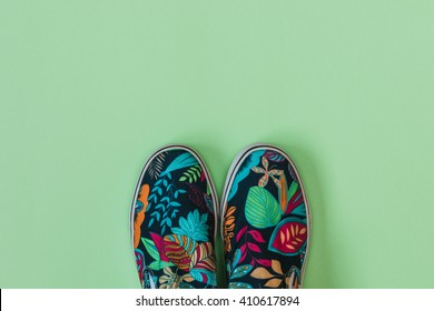 Flat lay fashion set: colored slippers shoes with palm and flowers print on pastel background. Top view.