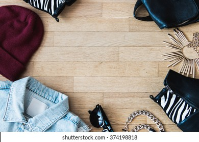 Flat lay fashion set : Jean jacket, sunglasses, hat, leather backpack, shoes and accessories. Negative space in the middle