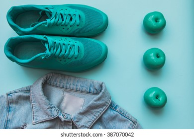 Flat lay fashion set : jean jacket, green sneakers and apples on light-blue pastel background