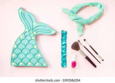 Flat lay fashion set: Mint colour mermaid tail and accessories make up brushes, sequin bracelet, nail