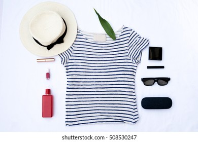 Flat lay fashion set, sunglasses, hat, leather backpack, accessories. Negative space in the middle