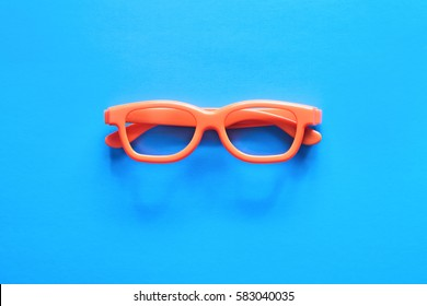 Flat lay fashion set: sunglasses on pastel backgrounds. Fashion summer is coming concept. Orange glasses on a blue background, top view. Trendy minimal style with colorful paper backdrop.