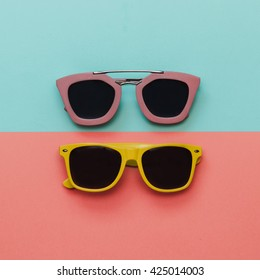 Flat lay fashion set:  two sunglasses on pastel backgrounds. Top view.