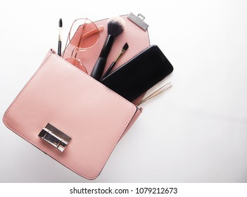 Flat lay of female fashion accessories and pink  handbag on white  background with copyspace. Beauty concept.