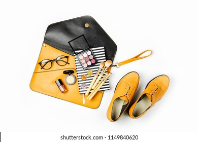 Flat lay of female fashion accessories, shoes, makeup products and handbag on orange colors. Beauty and fashion concept