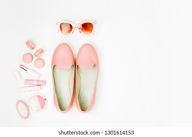 Flat lay of female fashion accessories, shoes, makeup products  on pastel color background. Beauty and fashion concept