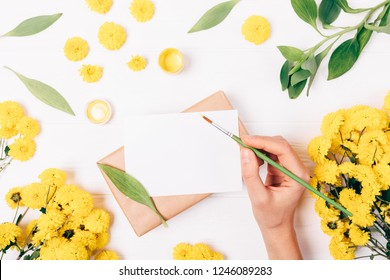 Flat lay female hand holding brush next to clean greeting card and paint among bright yellow flowers and green leaves on white background, top view.