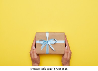 Flat lay of female hands holding handmade present on yellow background