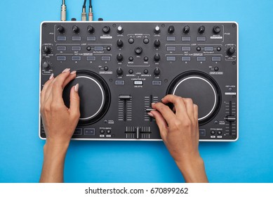 Flat lay of female hands playing DJ mixer on blue background
