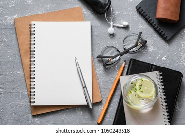 Flat lay female office table with business education accessories - notepad, tablet, glasses, earphones and a glass of refreshing lemon thyme lemonade. On a gray background, top view