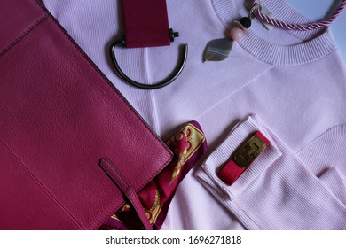 Flat lay of female pink fashion accessories,  products and handbag on pink cloth. Beauty and fashion concept