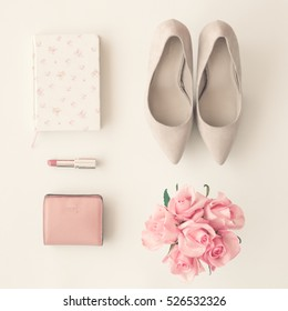 Flat lay of femenine items including heel shoes, wallet, lipstick, book and roses