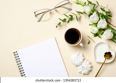 Flat lay feminine accessories, glasses, blank paper notepad, coffee cup, marshmallow and white roses flowers on pastel colors beige background. Top view beauty blogger desk with diary and female stuff