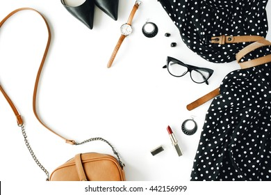 flat lay feminine clothes and accessories collage with black dress, glasses, high heel shoes, purse, watch, mascara, lipstick, earrings on white background.