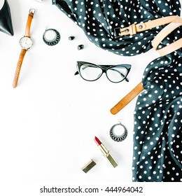 flat lay feminini clothes and accessories collage with black dress, glasses, high heel shoes, purse, watch, mascara, lipstick, earrings on white background.