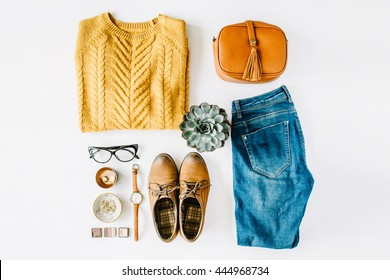 flat lay feminini clothes and accessories collage with brown cardigan, jeans, glasses, watch, earrings, purse, boots and succulent on white background.