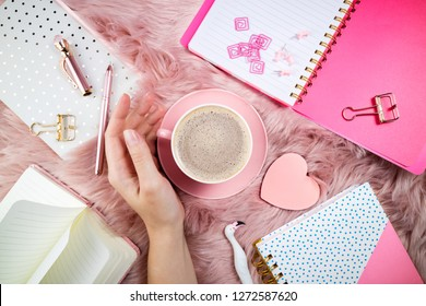 Flat lay femininity background. Female hand, coffee cup, notebooks and office supplies on pink woolen fur. Breakfast, domestic life, weekend and cozy atmosphere concept