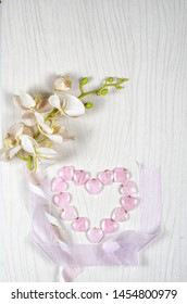 Flat lay flower and stone composition consists plastic orchid, silk ribbons and 14 rose quartz hearts which are laid out in the shape of a big heart. Top view, copy space.