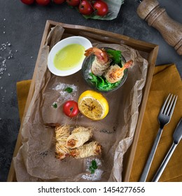 Flat lay food concept. King prawns in dough Kataifi on a wooden box on parchment paper top view. Lemon, herbs, cherry tomatoes, spoon, fork and yellow tablecloth