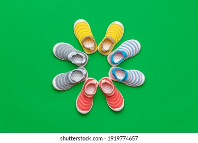 Flat lay with four pairs of multicolored children's shoes isolated on a green colored background. Colorful shoes arranged in a circle.