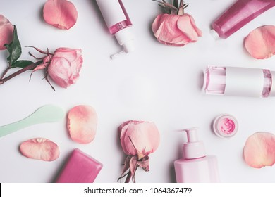 Flat lay frame of flowers and cosmetics products with Rose essential oil: toner,serum, essence,moisturizer and others on white desktop background, top view, banner. Facial Skin care beauty