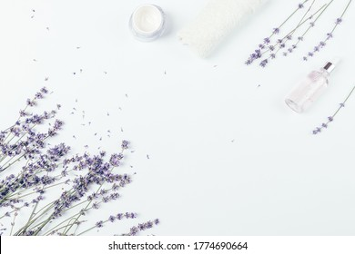 Flat lay frame lavender flowers with natural organic cosmetics and towel on white table.