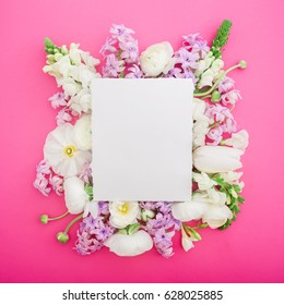 Flat lay frame with paper card, white ranunculus, snapdragon, tulip and freesia isolated on pink background. Top view