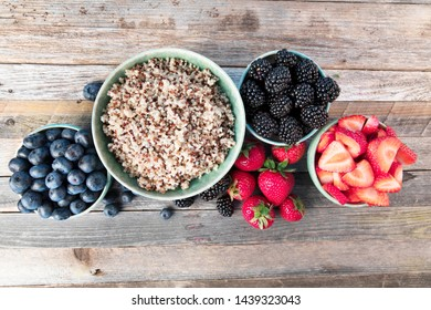 Flat lay of fres strawberries, blueberries, blackberreis and quinoain bowls.