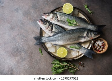 Flat lay fresh raw fish seabass in a plate with ice cubes, rosemary and lime on a dark rustic background. Top view, copy space