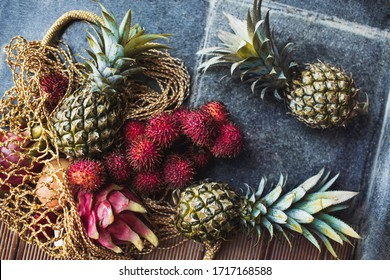 Flat lay of fresh tropical fruits pineapple, rambutan, dragon fruit in reusable mesh bag. Zero waste lifestyle. Raw healthy food and vegetarian diet. Taste of summer.