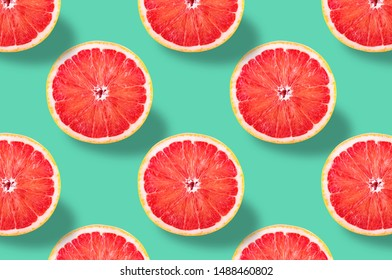 Flat lay fruit pattern of fresh grapefruit slices on green background. Minimal summer fruits pattern for blog or recipe book